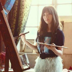 絵をカンバスに描く女性